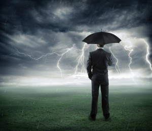 risk and crisis - businessman below storm with umbrella